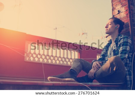 Young and handsome man relaxing on the roof and listening music on his mobile phone (intentional sun glare and vintage color) - stock photo