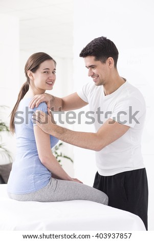 Young and handsome physiotherapist massaging his patient's arm, sitting in light interior