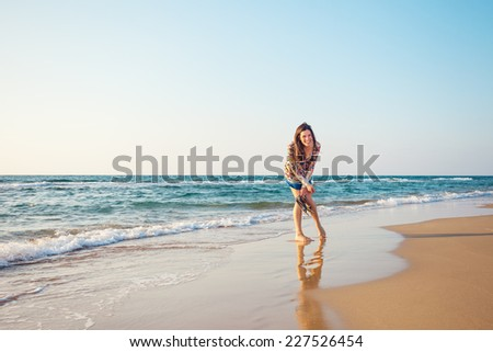 young and handsome woman laughing and standing on the sand near the blue ocean - stock photo