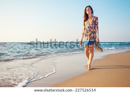 young and handsome woman walking on the sand and looking far away near the ocean - stock photo