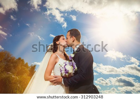 Young and happy bride and groom in wedding clothes outdoor near the river