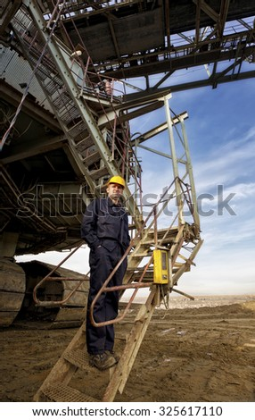 Young and happy coal mines worker with a helmet on his head looking over the camera and smiling. - stock photo