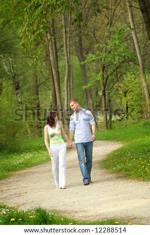 young and happy couple taking a walk in a park