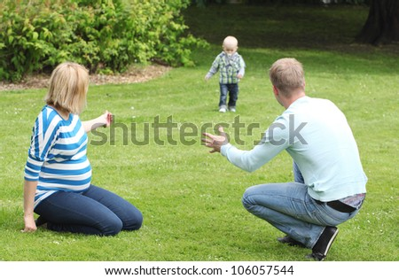 Young and happy family have fun in the park - stock photo