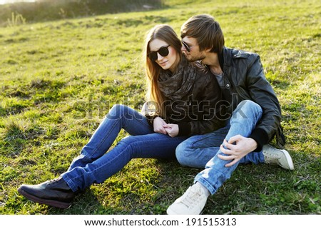 Young and happy family relaxing in the park on the grass