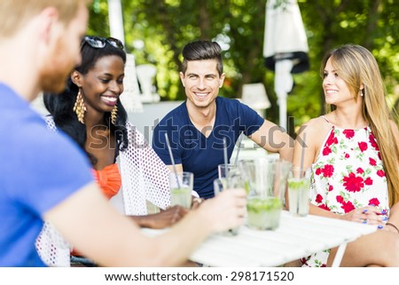Young and happy friends sitting talking at a table outdoors and smiling - stock photo