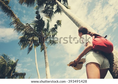 Young and happy girl standing near palm tree at resort on holidays (intentional vintage color)  - stock photo