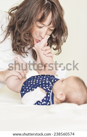 Young and Happy Mother Having Good Time Together with Her Baby Infant. Vertical Image - stock photo