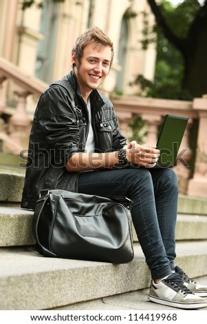 Young and happy student with laptop sitting on a stairs - stock photo