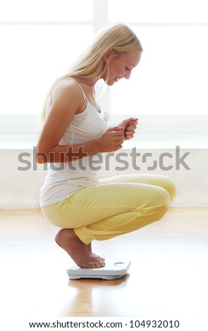 Young and happy woman with weight scales - stock photo