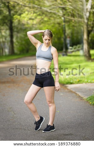 young and healthy active model posing in the park with tights and tank top - stock photo