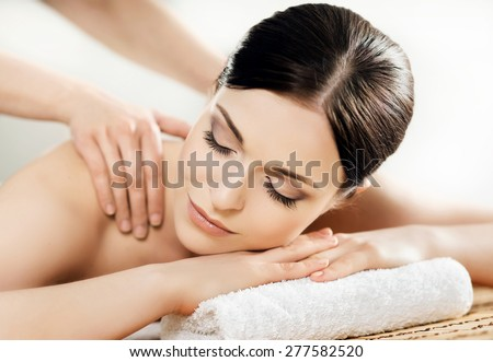 Young and healthy woman in spa salon. Traditional Swedish massage therapy and beauty treatments.  - stock photo