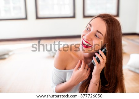 Young and healthy woman talking phone during the break in the sport gym after practising yoga
