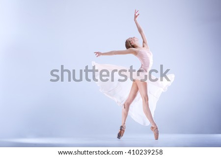 Young and incredibly beautiful ballerina is posing and dancing in a white studio full of light. The photo greatly reflects the incomparable beauty of a classical ballet art.