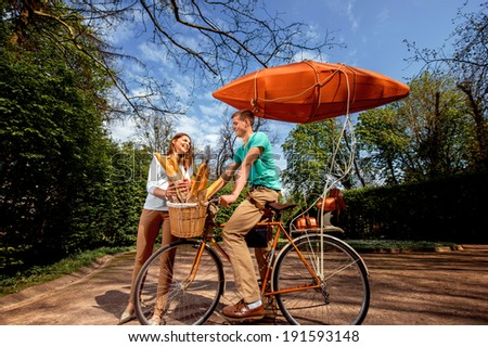 Young and joyful couple having fun in the park with bicycle  - stock photo