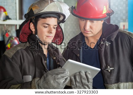 Young and mature firemen using tablet computer at fire station