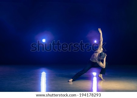 Young and muscular man performing a contemporary dance pose on a stage.