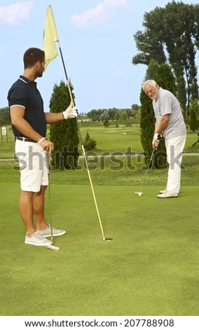 Young and old golfer playing together. - stock photo