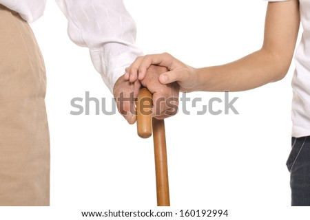 Young and old hands on cane together closeup against white background - stock photo