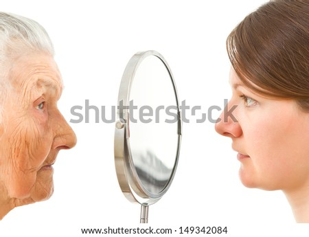 young and old  isolated faces standing on the two sides of the  mirror - stock photo