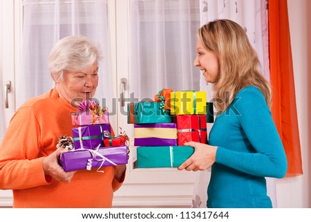 young and old woman are giving presents to each other