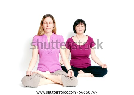 Young and old woman sitting in lotus seat practicing yoga together - stock photo