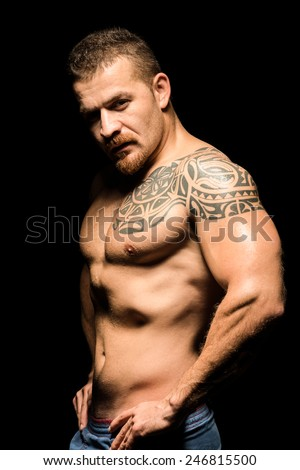 Young and powerful attractive male model with competitive pose and mean look - stock photo
