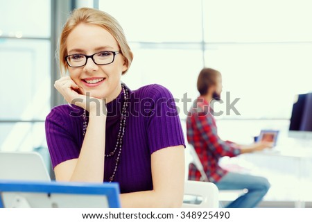 Young and pretty business woman working in office - stock photo