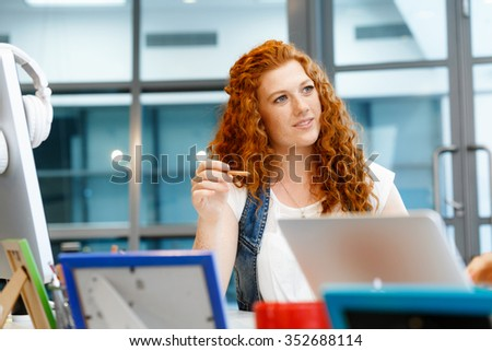 Young and pretty business woman working in office