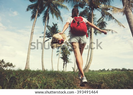 Young and pretty girl with outspread hands walking at sunny day near palm trees (intentional vintage color)  - stock photo