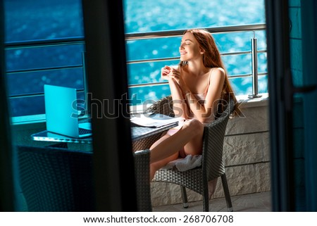 Young and pretty woman enjoying morning on the balcony near the sea. - stock photo