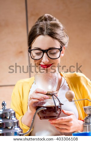 Young and pretty woman holding chemex with brewed coffee sitting at the wooden table with various stuff for alternative coffee brewing.