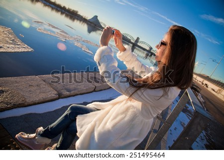 Young and pretty Woman taking photo with her smartphone, early morning winter landscape with sunrise and ice floats.