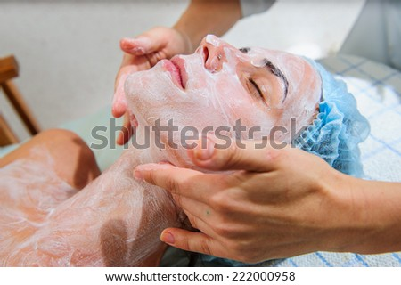 Young and relaxed woman getting a face massage.