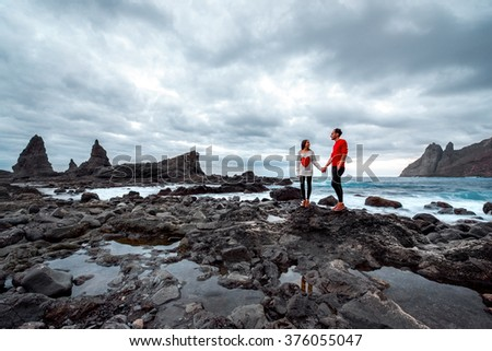Young and romantic couple in red sweaters standing together and holding hands on the rocky coast on the cloudy weather. Wide angle image, general plan with copy space