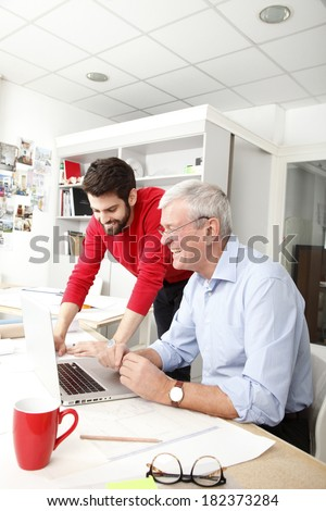 Young and senior businessmen working together in small architect studio. - stock photo