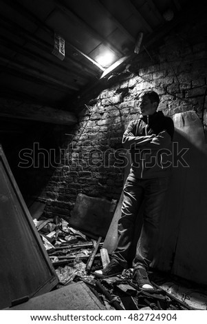Young and serious man in the old, ruined factory