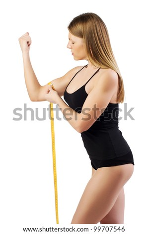 Young and sexy blond woman measuring her arm muscle by measure tape, isolated over white background