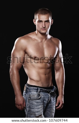 Young and sexy guy wearing jeans over black background - stock photo