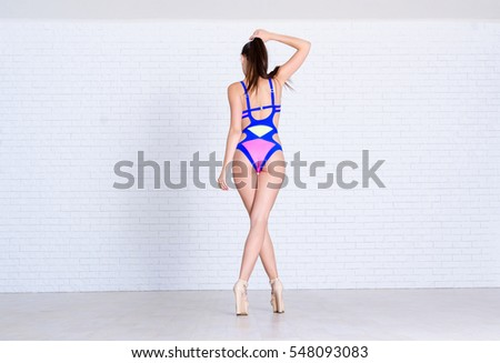 Young and sexy model in the colorful swimsuit. Photos of woman in fashion poses, she is in swimming suit and on the heels.