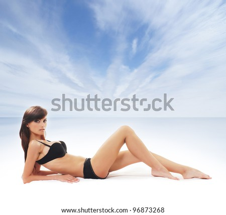 Young and sexy woman in swimsuit near the sea - stock photo