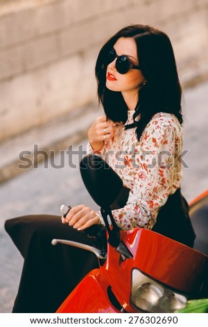 Young and sexy woman with her motor scooter - stock photo