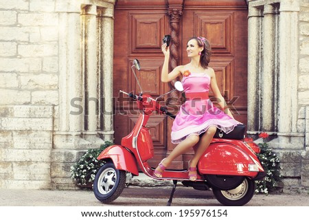 Young and sexy woman with her motor scooter and a vintage photo camera - retro style image. - stock photo