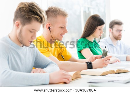 Young and smart students learning in a classroom - stock photo