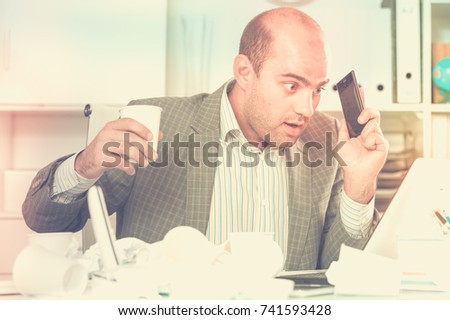 Young and smiling man office worker deciding and talking on the phone