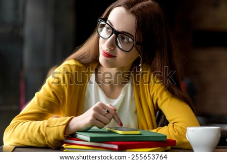 Young and smiling woman using smart phone on the colorful books in the dark interior background - stock photo