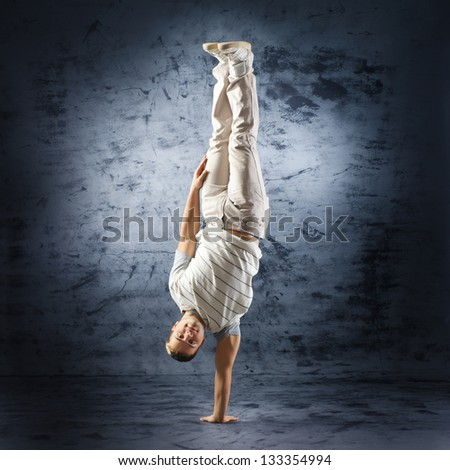 Young and sporty modern dancer over the dramatic background - stock photo