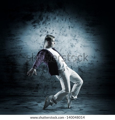 Young and sporty modern dancer over the dramatic background in monochromatic style - stock photo