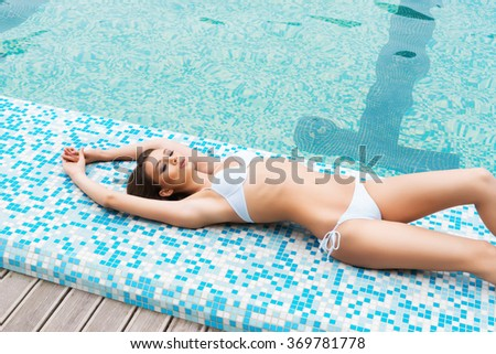 Young and sporty woman in swimsuit. Girl relaxing in a pool at summer. - stock photo