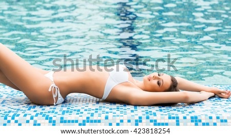 Young and sporty woman in swimsuit relaxing in a pool